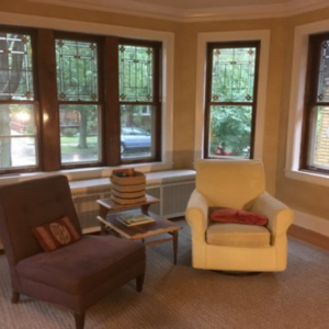 Living room in West Ridge, multiple restored double hung windows.